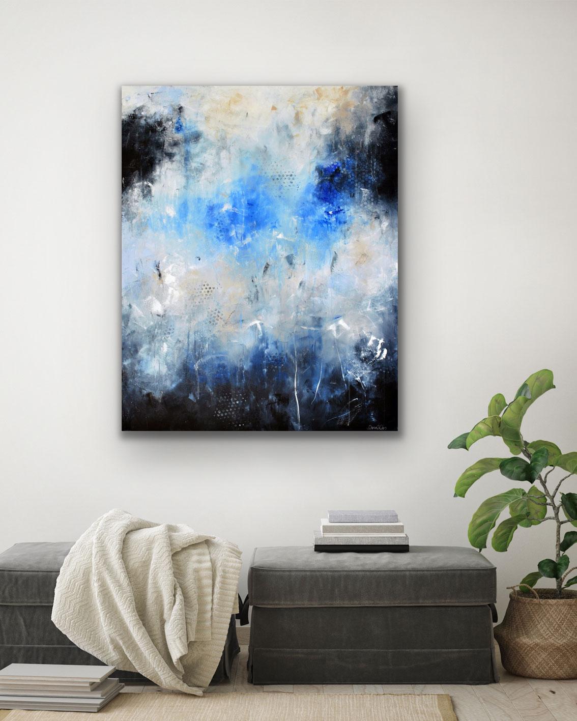 Abstrakt målning mörkblå beige grå blå på vägg ovanför fotpallar med filt och böcker med en grön växt bredvid