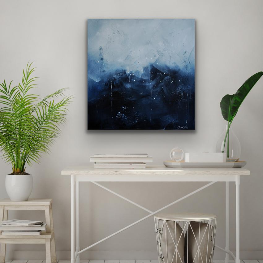 Abstrakt akrylmålning i blå nyanser på vägg i sovrum med lampa och bänk i rotting